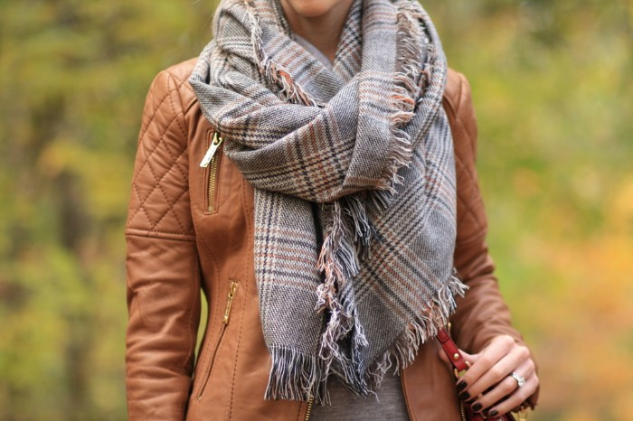 how to wear a square scarf, in light grey, with a plaid pattern, over a brown leather jacket