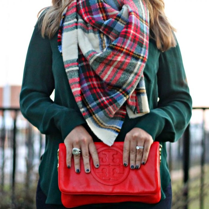 leather bag in red, with a big round embossed logo, held by a woman, in a dark green jumper, accessorized with a plaid blanket shawl, folded around her neck
