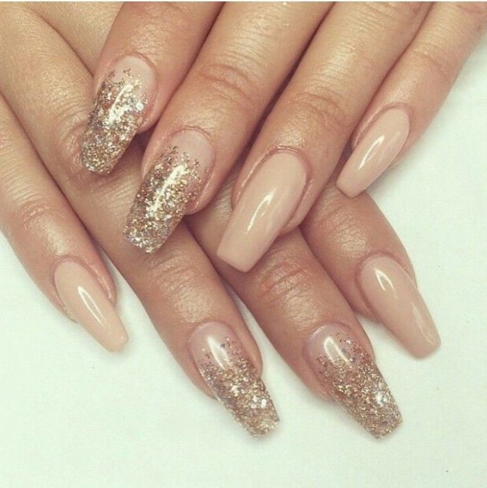 ballerina shaped manicure, long with square tips, covered in gold glitter, pink nude nails, on two hands