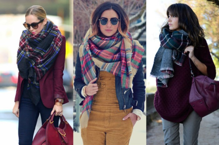big patterned scarves, worn around the necks, of three women, two dressed in jeans, and one sporting beige corduroy overalls, how to fold a blanket scarf, in the winter