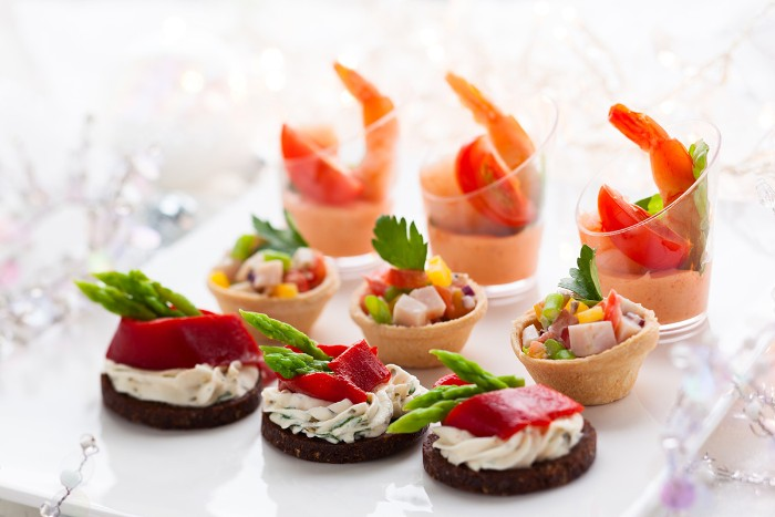 nine colorful hors dourves, prawn cocktails in small glasses, tiny edible baskets with veggies, crackers with creamy spread, peppers and asparagus