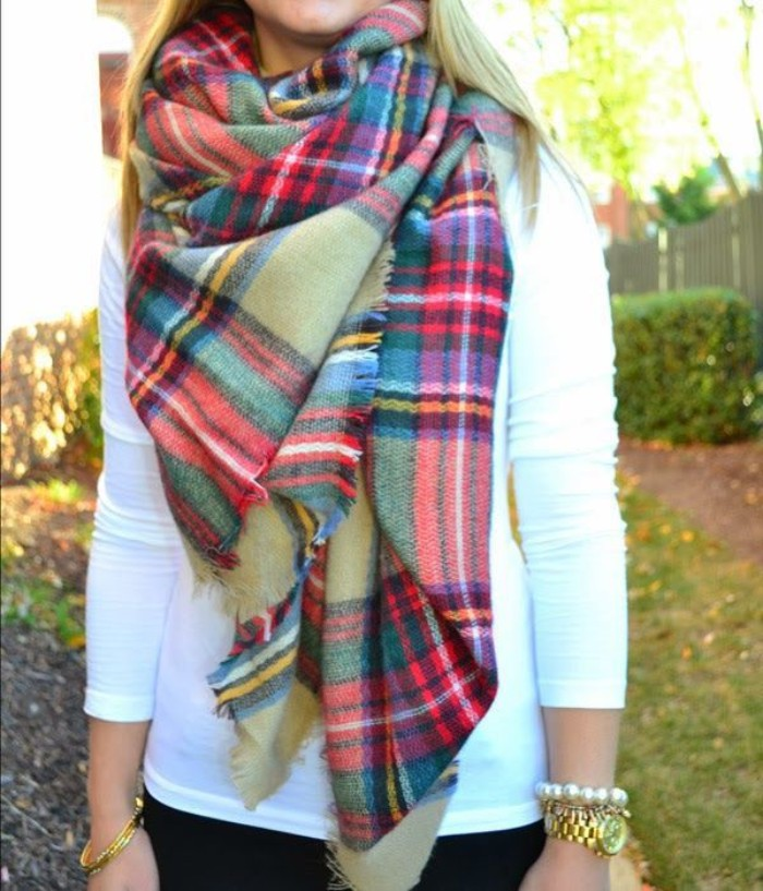 yellow and white, black and green, red and blue stripes, on a pale kahki green tartan scarf, worn over a white jumper, how to wrap a blanket scarf