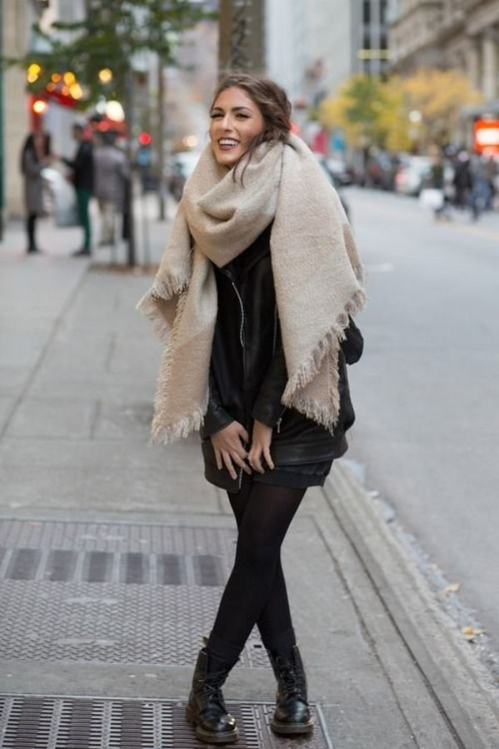 soft cream oversized scarf, with small tassels, worn over a black outfit, by a laughing brunette woman, standing in the street