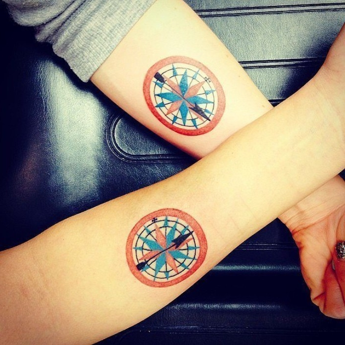 round tattoos in red and white, with blue and black details, depicting two matching compasses, husband and wife tattoos, on the lower part, of two crossed arms