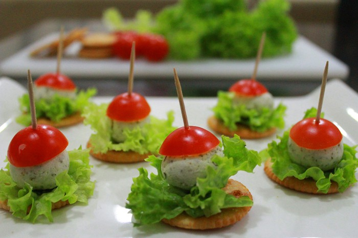 appetizers for a crowd, feta cheese balls, with small lettuce leaves, and cherry tomoato halves, skewered with toothpicks