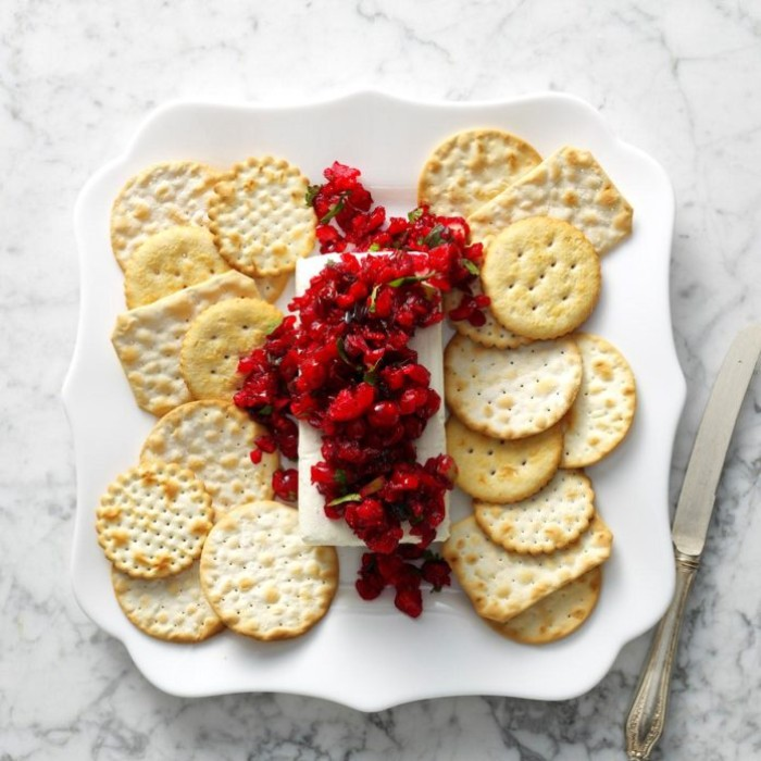cranberry confit and brie chiese, on a white ceramic plate, containing various kinds of crackers, appetizers for a crowd, for christmas or thanksgiving