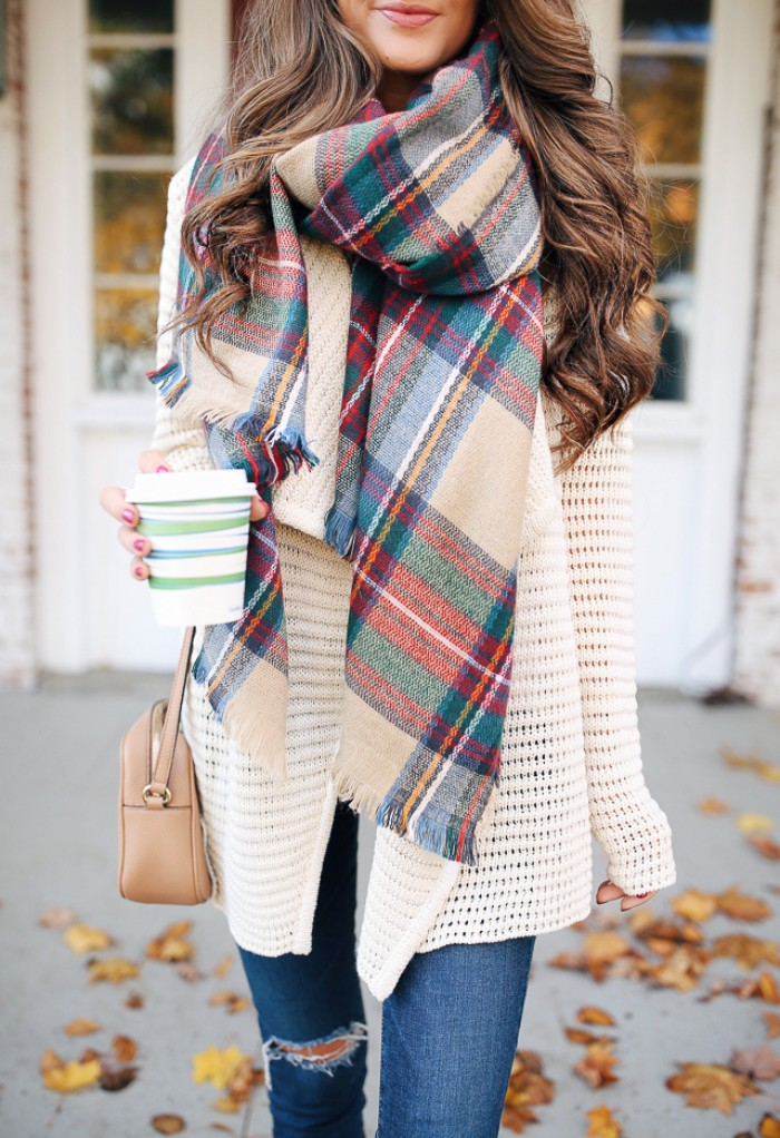 beige and red, green and blue, grey and white plaid scarf, worn with an off-white knitted cardigan, and distressed skinny jeans, how to tie a blanket scarf, by a smiling brunette woman