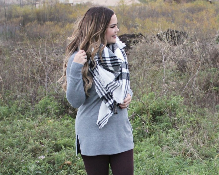 tunic sweater in pale grey, worn over black leggings, by a woman with light brunette hair, in loose curls, white and grey oversized scarf