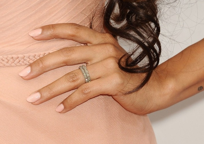 brunette curly dark hair, falling over a hand, placed on a woman's hip, pale nude pink nail polish, and dress in a matching color
