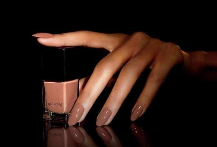 mocha-colored nail polish, on a hand with long, slender fingers and oval nails, with a nail polish bottle