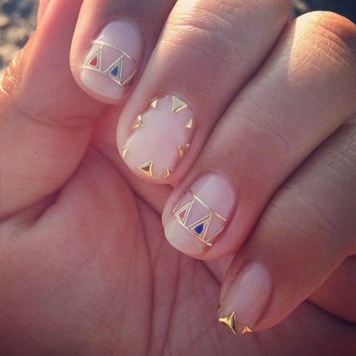 red and blue and gold nail decal stickers, on a short manicure, with pink nude nails, seen in close up