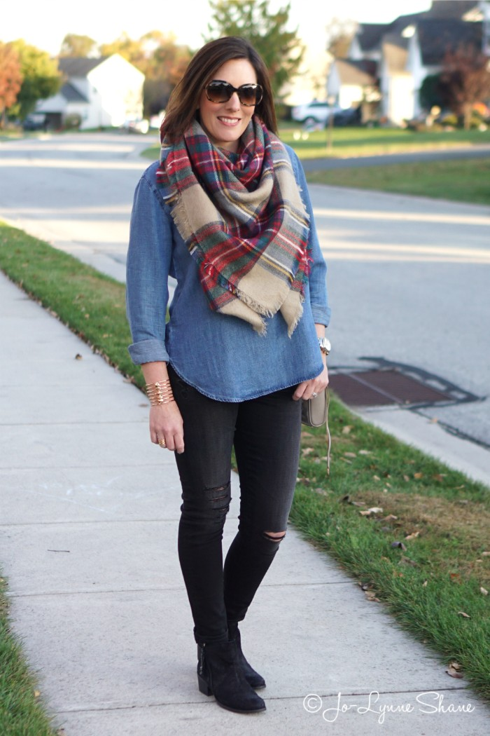 sunglasses worn by a brunette woman, in a denim shirt, and ripped black skinny trousers, with a beige plaid scarf around her neck