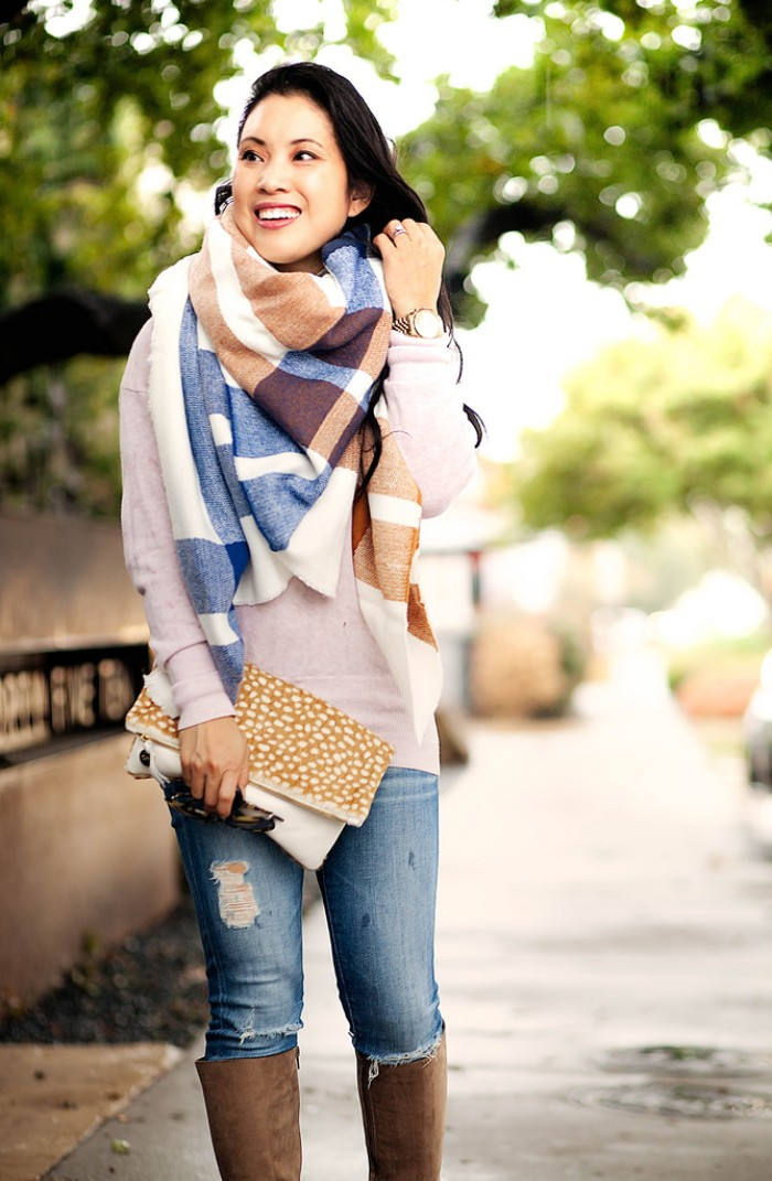 ripped blue jeans, worn with an off-white jumper, and a bulky blanket shawl, by a smiling east asian woman, holding a clutch bag