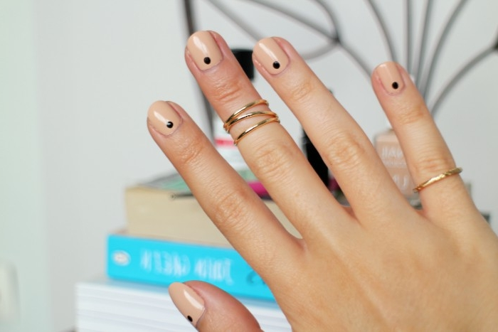 points in black, on a short and square manicure, painted with a glossy, nude pink nail polish