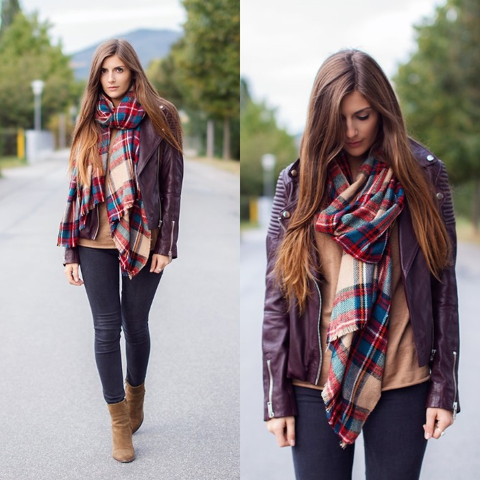 how to tie a blanket scarf, demonstrated by a slim brunette woman, wearing dark skinny trousers, and a brown leather biker jacket, seen from two angles