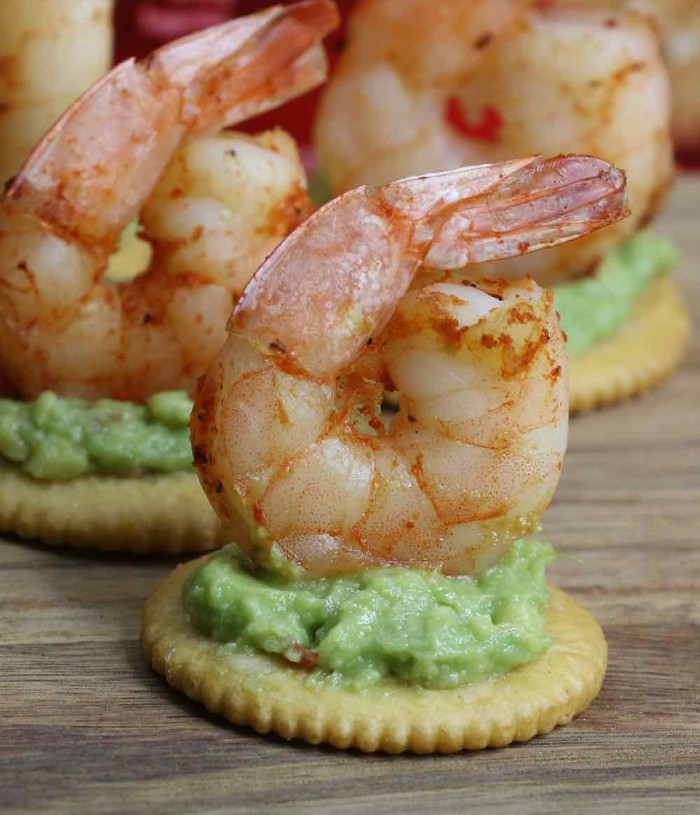hor dourves, grilled seasoned prawns, topping several ritz crackers, with a mushy, green avocado spread