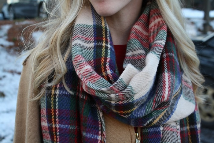 camel colored coat, worn with a plaid scarf, by a blonde woman, with long wavy hair, how to wear a blanket scarf, snow in the background