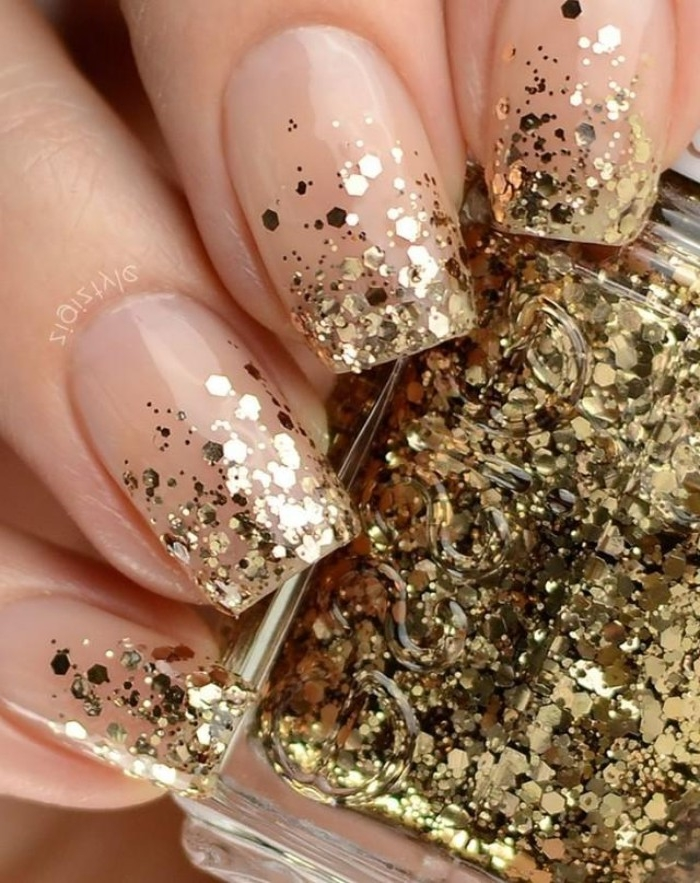 flakes of gold glitter, decorating the tips of four square nails, nude nails with glitter, on a hand holding a bottle, of gold glitter nail polish