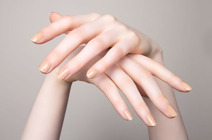 peach colored nude nail polish, on the short, square nails of two very pale hands