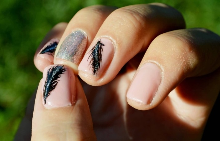 black feathers painted on short, square pink nails, decorated with silver glitter, best nude nail polish