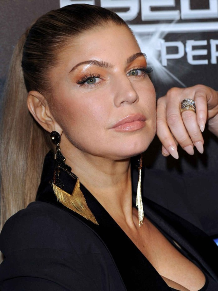the singer fergie, dressed in black, and wearing large black and gold earrings, long stiletto nails, painted in a nude color