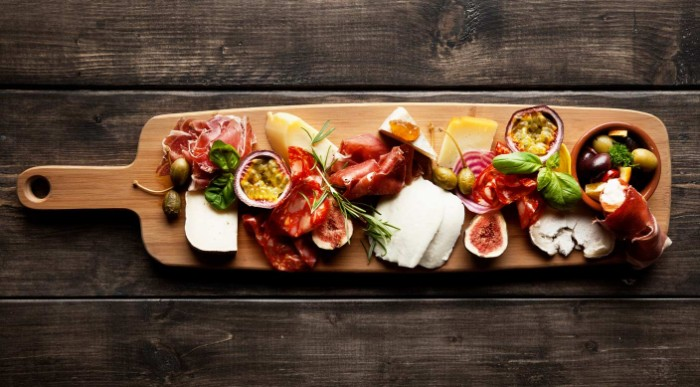 long wooden board, with feta cheese, passion fruit and figs, prosciutto and salami, and many others hor dourves