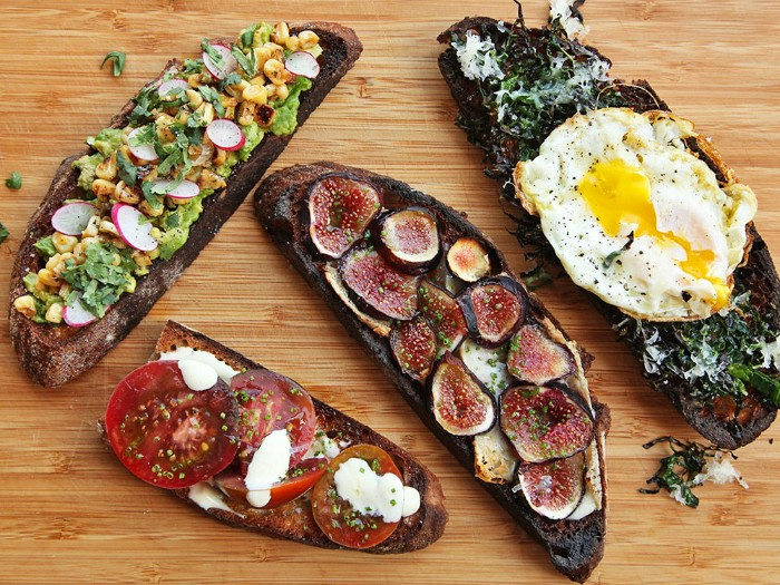 large slices of bread, covered with different toppings, hor d oeuvres with guacamole and radish, tomato and mozzarella, figs and egg