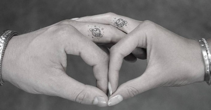 planets with hoops arround them, surrounded by tiny stars, minimalistic matching couple tattoos, done on two fingers, belogning to two linked hands