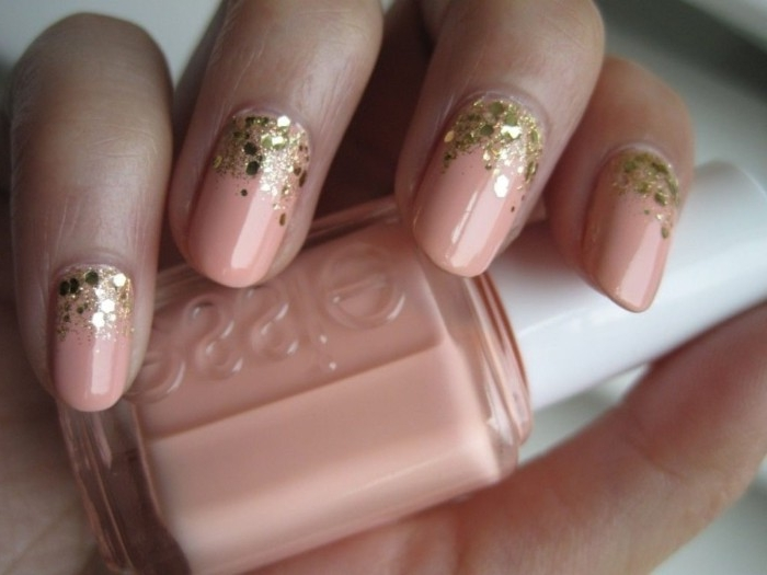 glitter flakes in gold, decorating the base of four oval nails, covered in pink nail polish, nude nail designs, on a hand, holding a nail polish bottle