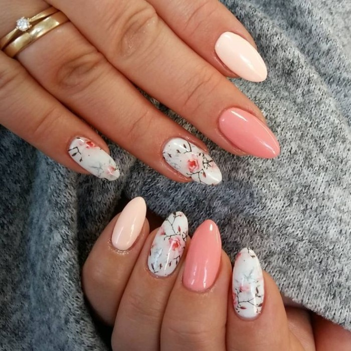 light nail polish in blue, decorated with floral motifs, and in two shades of pink, on two hands, with oval shaped nails,