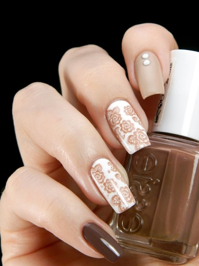 brown nail polish, in a small bottle, held by a hand, with long square nails, decorated with brown, white and nude nail polish, and flower shaped, nail decal stickers