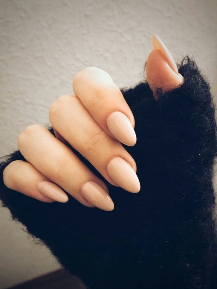 classic manicure with sharp, oval nails in pale pink, best nude nail polish, hand in a oversized, fluffy black sleeve
