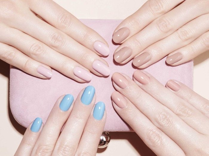 three hands with different, nude gel nails, pink and beige hues, and one hand with teal blue manicure