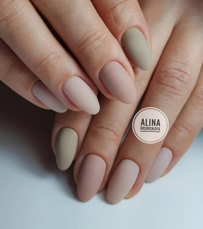 shades pf pastel pink, and grey matte nail polish, on the oval manicure of two hands