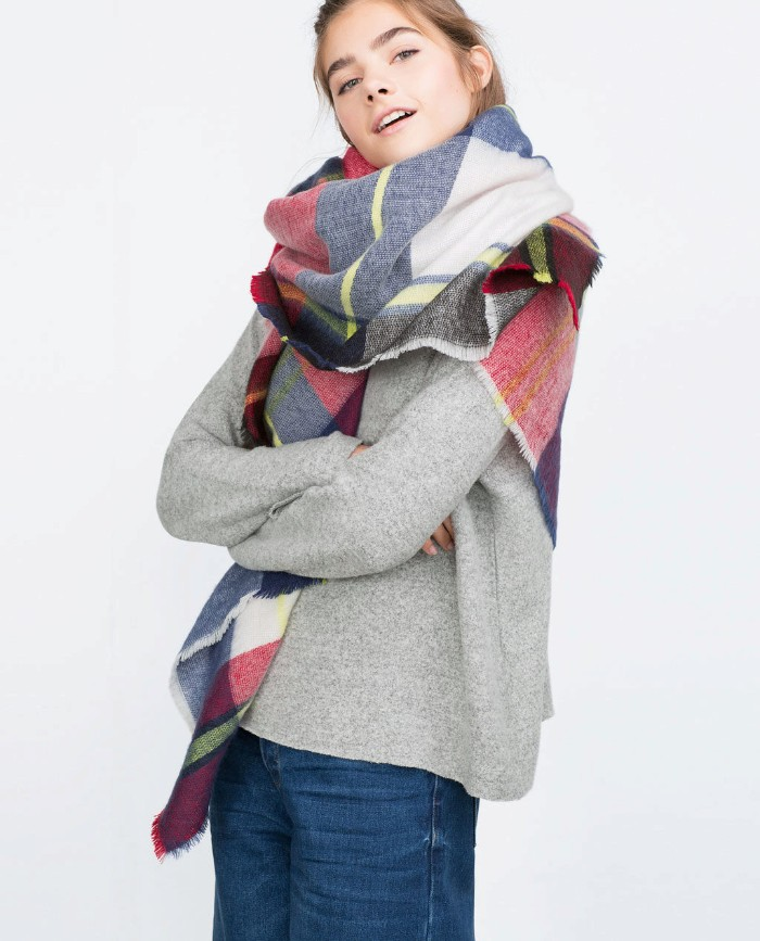 how to wear a blanket scarf, smiling young woman, with arms crossed, wearing a pale grey jumper, dark blue jeans, and an oversized scarf, around her neck