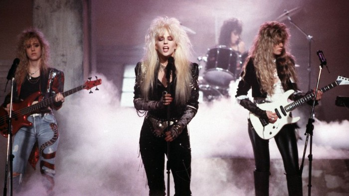 punk glam rock band, performing on a stage, 80s fashion trends, teased vouminous and messy hair, leather trousers and jackets, jeans with applique details