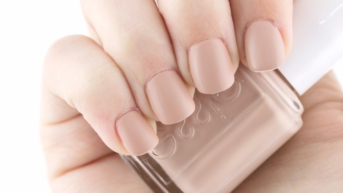 natural looking manicure, short and square nude matte nails, on a hand, holding a bottle of nail polish