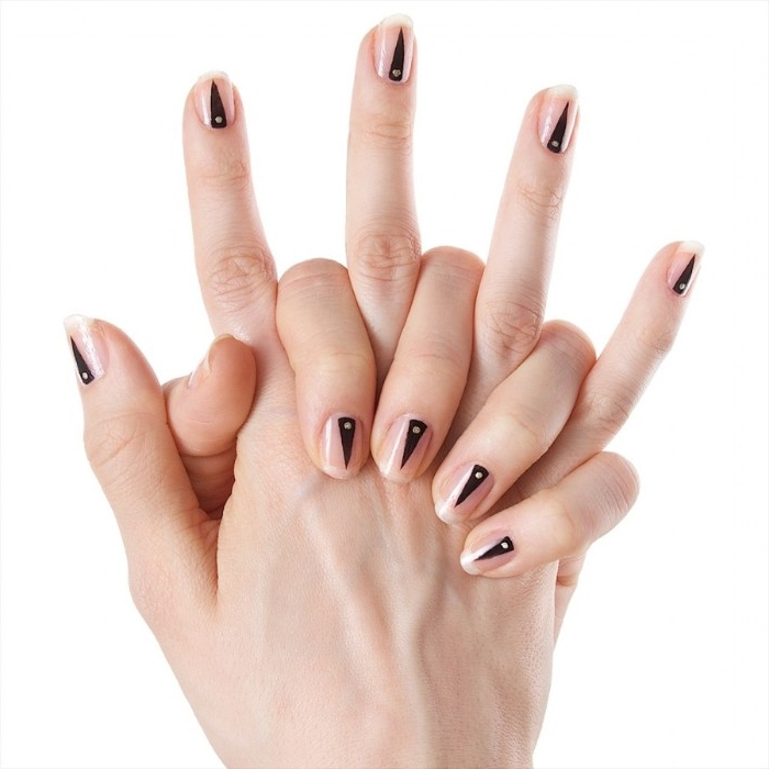 narrow triangles in black, each with a small white dot, painted on the short nude nails, of two hands