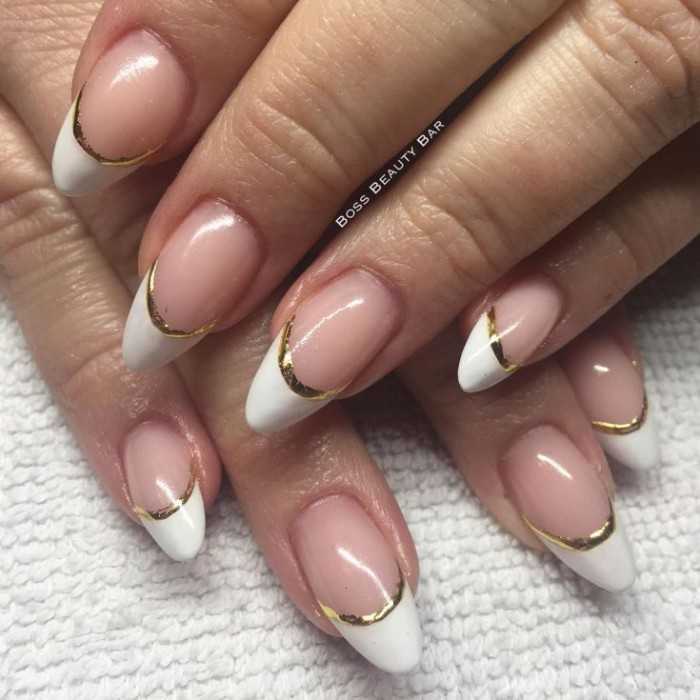 french manicure with gold details, on two pale hands, with medium to short pointy nails