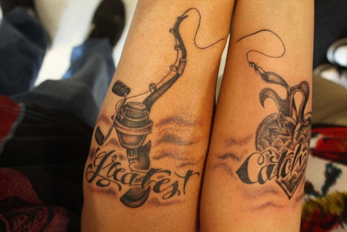 fishing rod with a hook, attached to a heart, with the inscription greatest catch, tattooed across two arms, placed next to each other, matching couple tattoos, done in black ink