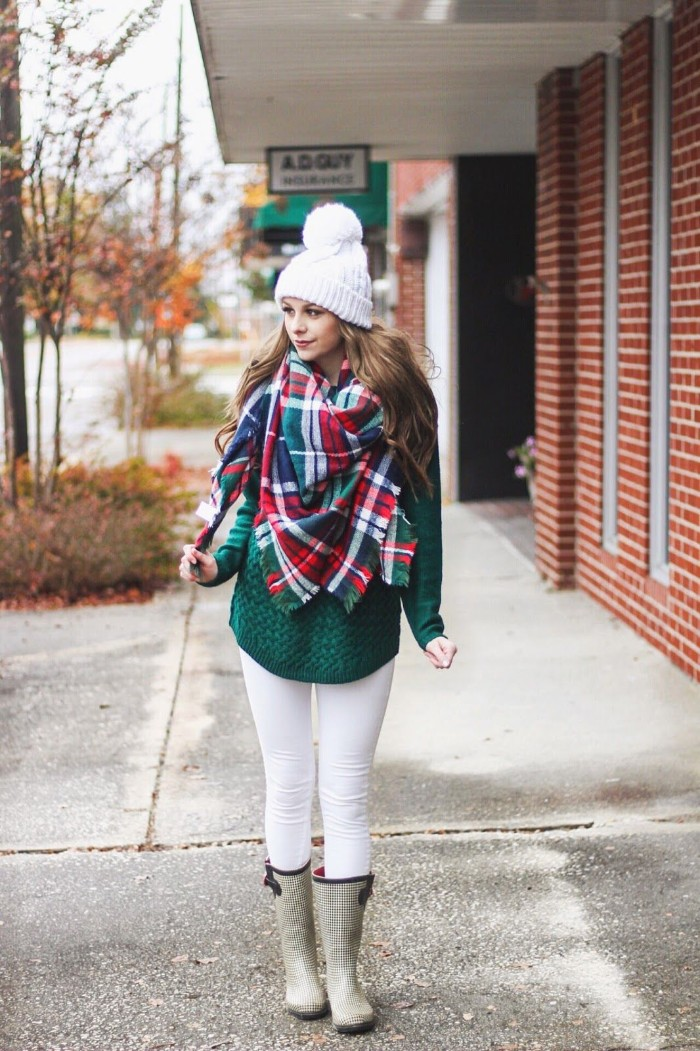 rubber rain boots, over white skinny trousers, and a green, cable knit jumper, worn by a brunette woman, in a white knitted beanie hat, her neck and shoulders covered by blanket shawl