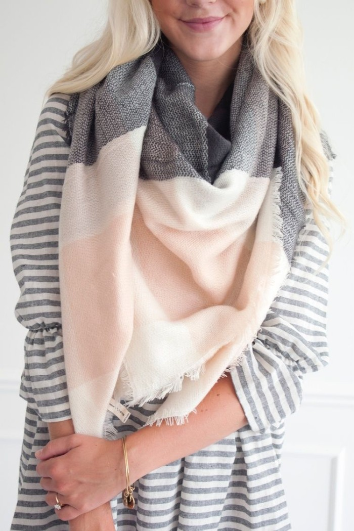 close up of a grey, white and pale pastel pink scarf, draped around the neck of a smiling, young blonde woman, how to wear a blanket scarf, with a striped blouse