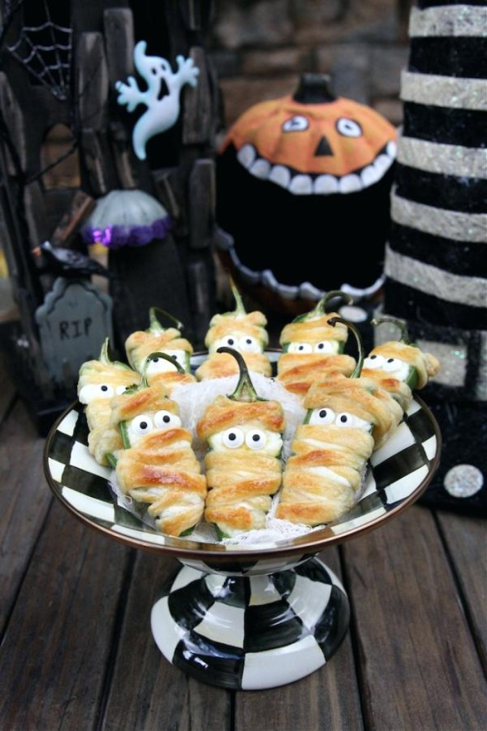 jalapeno poppers for halloween, wrapped in grilled cheese, and decorated with little eyes, resembling mummies or ghosts
