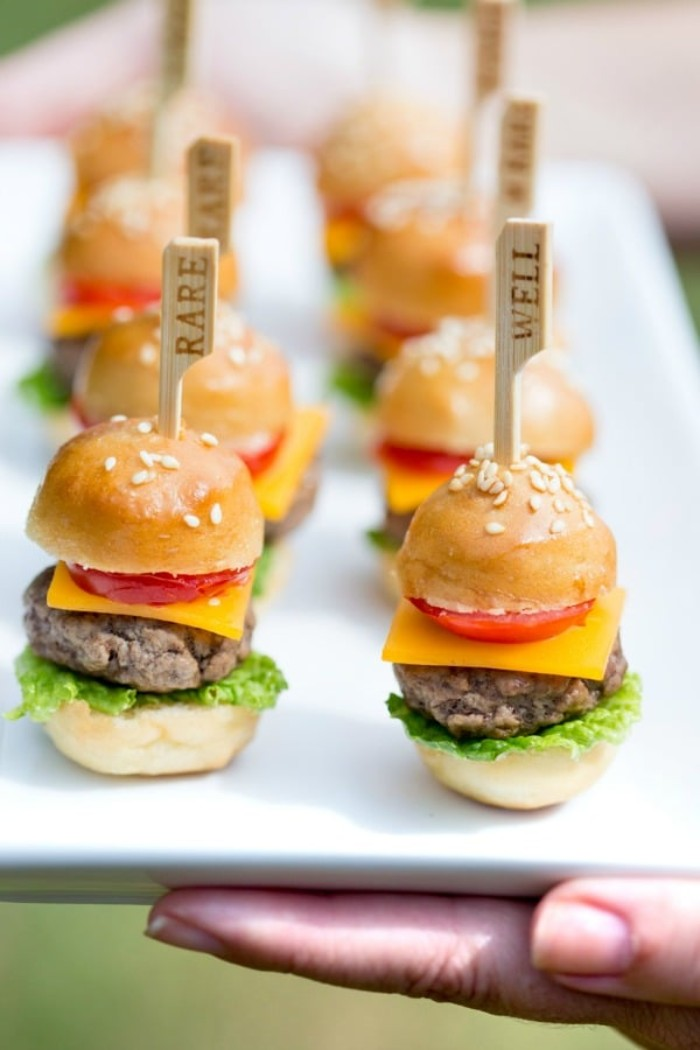 bite-sized hamburgers, on a white rectangular plate, horderves ideas. each burger contains a wooden cocktail stick, saying whether it's rare, or well done