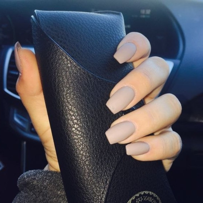 greyish-beige matte nail polish, on a square manicure, worn by a hand, holding a textured, black leather glasses case