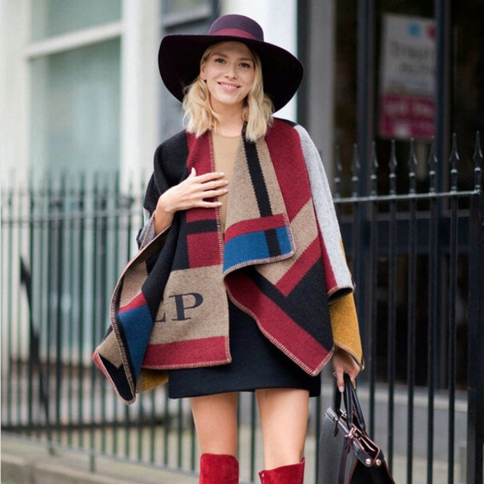 wide-brimmed purple felt hat, worn by a smiling blonde woman, wearing a black mini skirt, red over the knee boots, and a bulky oversized scarf, in block colors