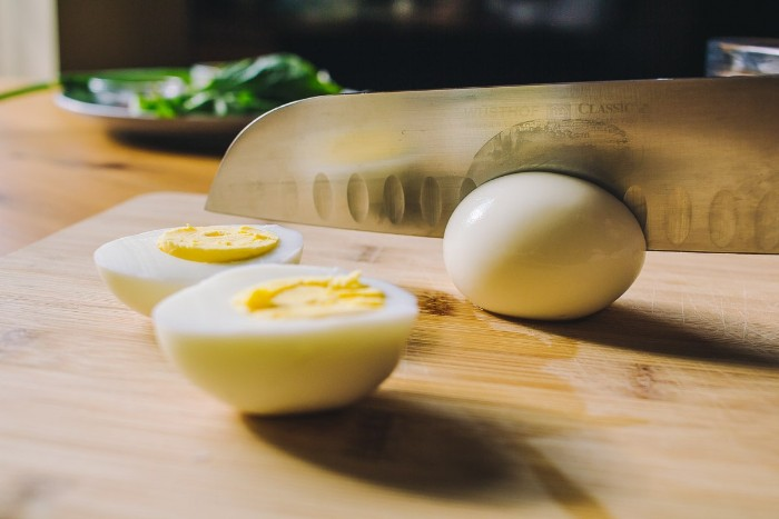 knife cutting through a hardboiled egg, how to make horderves, two halves of another egg nearby