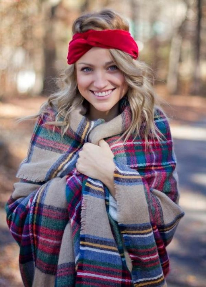 bright red headband, worn by a smiling, young blonde woman, bundled in an oversized, multicolored plaid shawl, how to fold a blanket scarf, when it's really cold