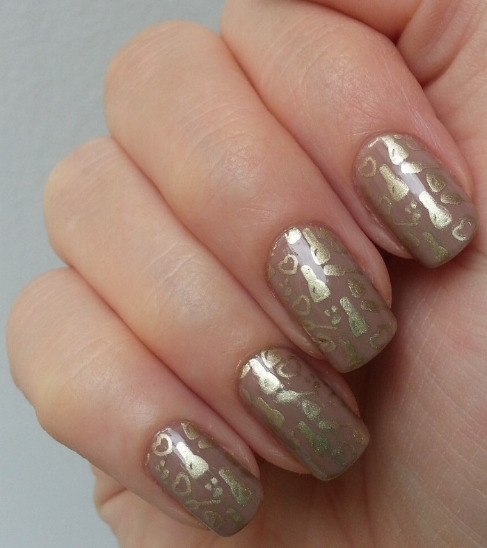 various shapes hand-drawn in gold, on four square nails, painted in beige nail polish