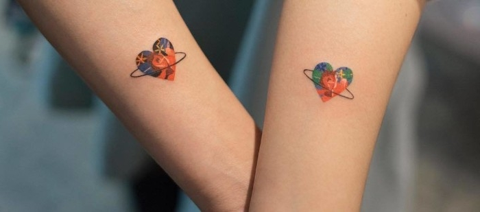 multicolored hearts with thin, black hoops around them, on the lower parts of two linked arms, matching tattoos